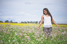 Woman walking through a field of flowers.