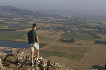 a man on a mountaintop looking out at farmland
