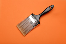 Paintbrush on an orange background.
