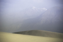sand dunes in a desert and distant mountains