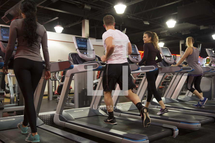 men and women walking on treadmills at the gym