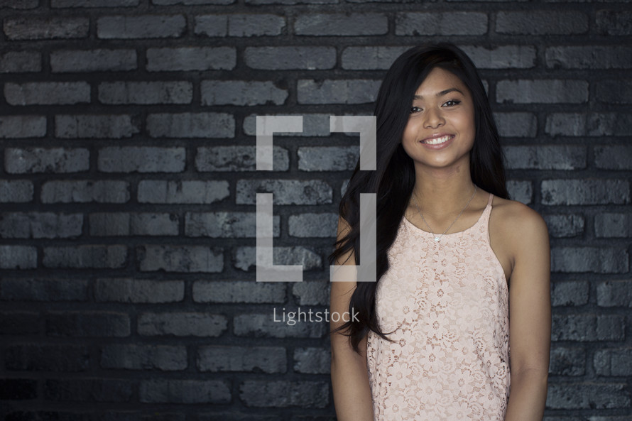 A smiling young woman standing against a gray brick wall.