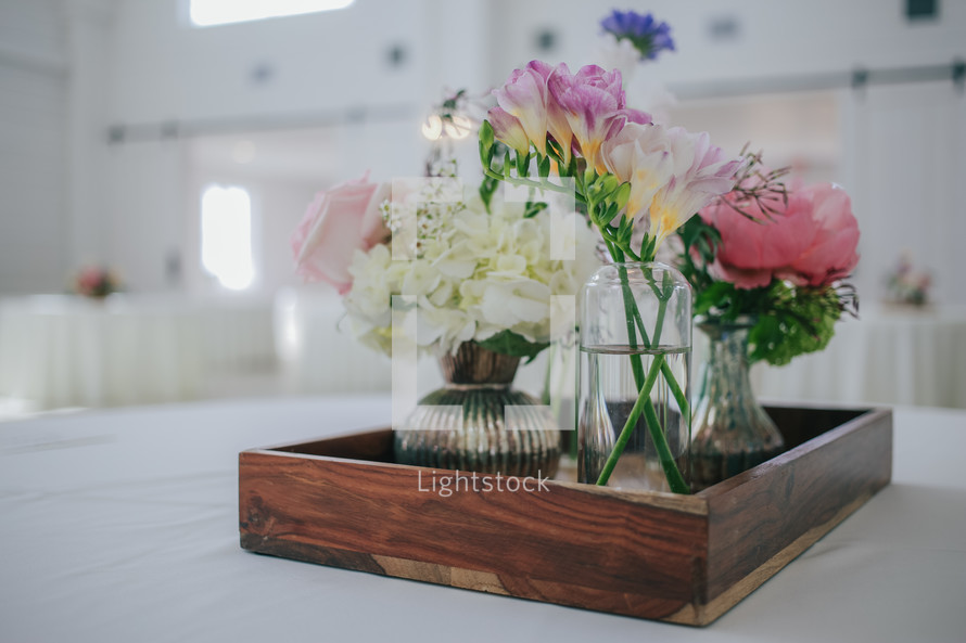 flowers in vases on a tray on a table