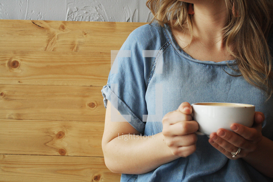 a woman with a coffee cup sitting in a both