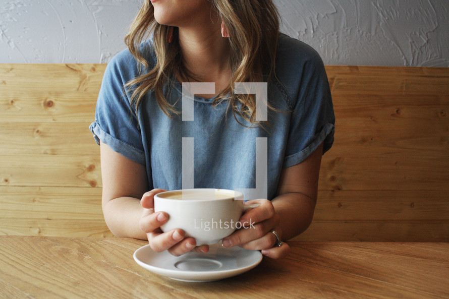 a woman with a coffee cup sitting in a booth
