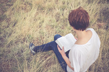 Woman sitting outside in a field of grass reading the Bible.