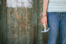 Teen holding a hammer near a half painted wood fence.