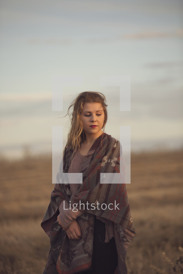 a young girl with blanket scarf in the evening sun