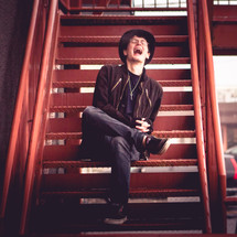 A laughing young man sitting on a metal staircase.