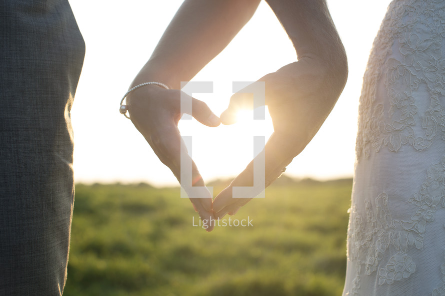 bride and groom making a heart shape with their hands