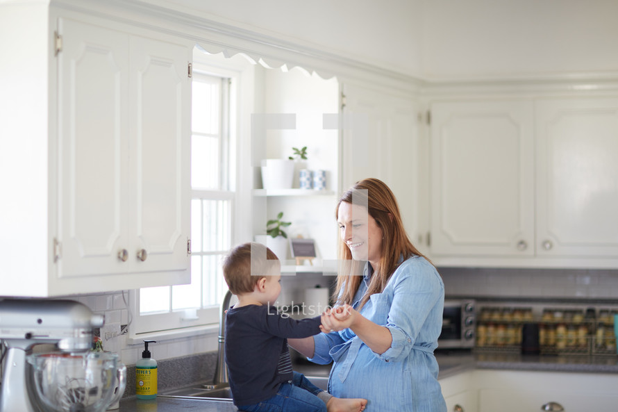 a mother in the kitchen with her toddler son