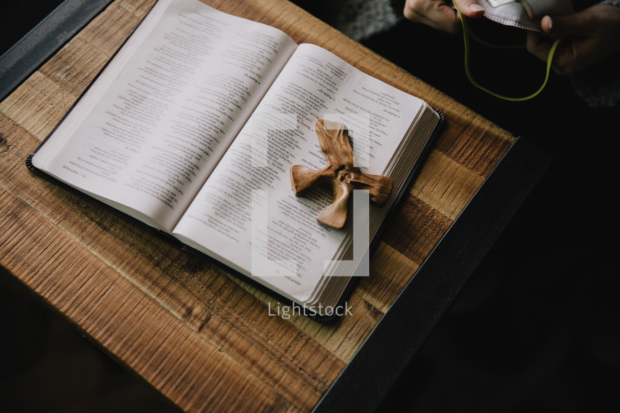 wood cross on the pages of a Bible