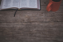 An open Bible and orange coffee mug on wood