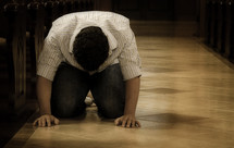 man kneeling on a church floor