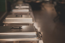 Stainless steel pans lined up for catering a meal.