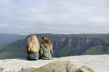 two women sitting at the top of a mountain
