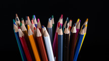 colored pencils on a black background with copy space