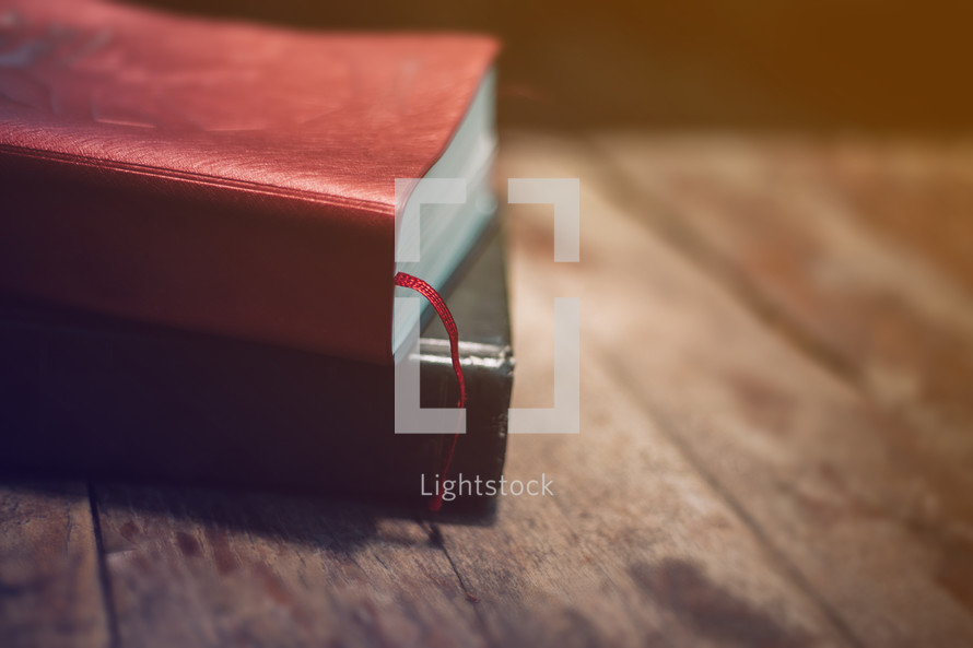 stacked Bibles on a wood table