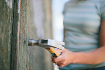 Hammer being held by a woman, hammering into a wooden wall