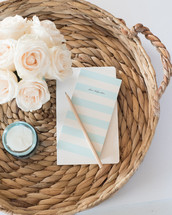 A pencil and notecard, candle, and white flowers on a rattan basket.