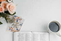an open Bible, mother's day card, coffee cup, and bouquet of flowers