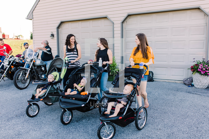 mothers standing together with babies in strollers