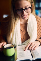 a woman reading a Bible and a coffee cup