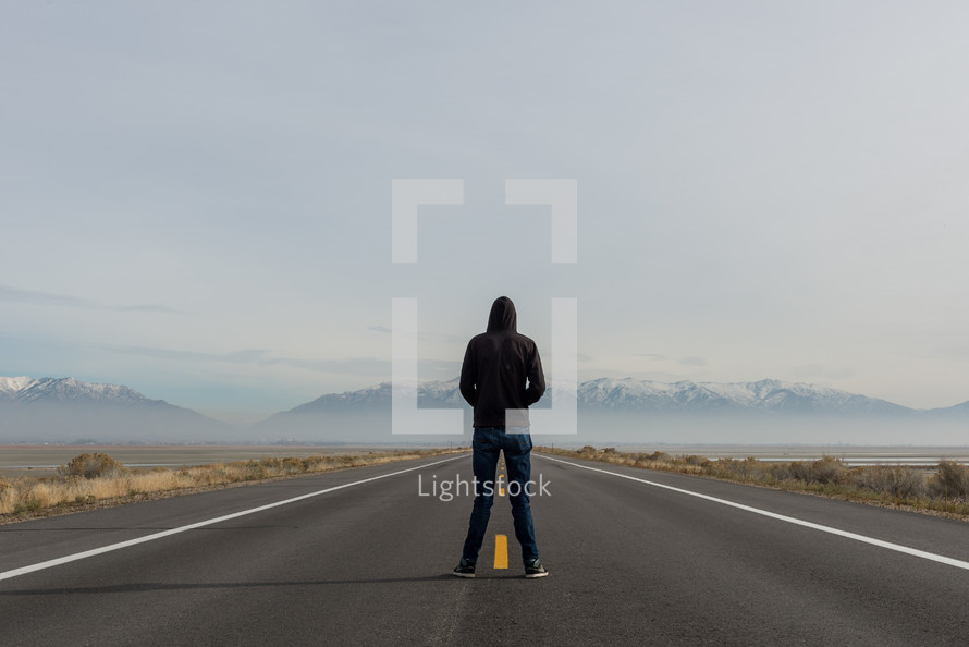 man in a hoodie standing in the center of a highway