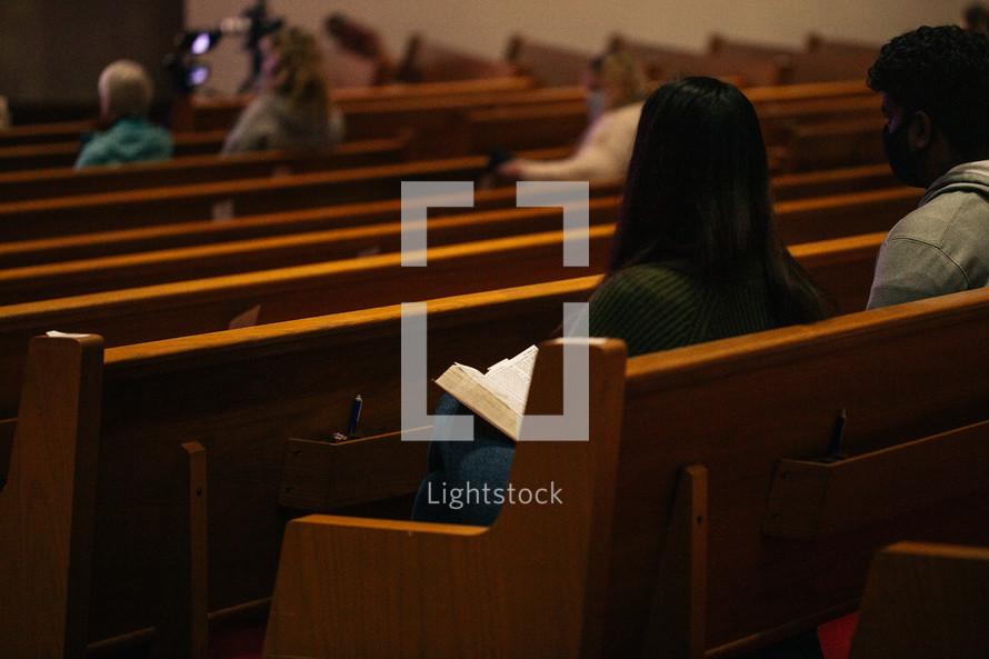 parishioners sitting in church pews