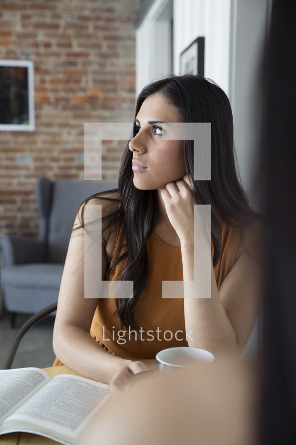 young woman sitting at a table thinking.