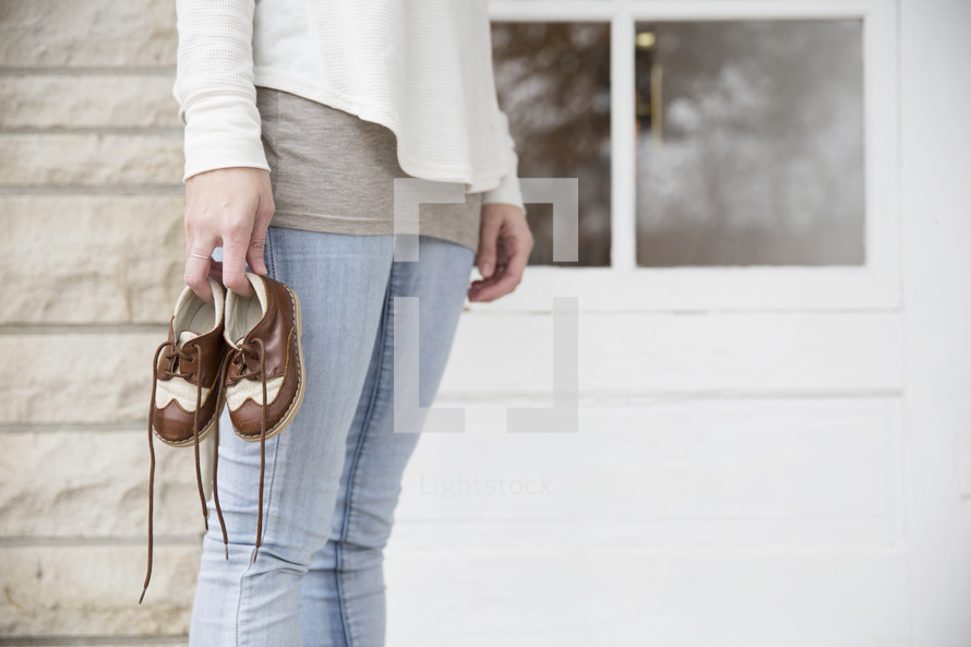 woman holding a toddler's shoes