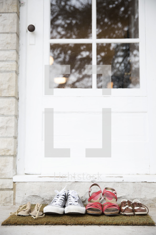 A family's shoes in front of a door on a doormat.