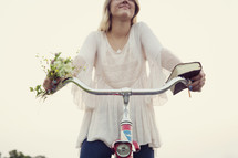 woman with flowers and a book holding onto handle bars of a bike