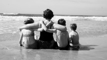 mother and children sitting on a beach letting the tide wash over them