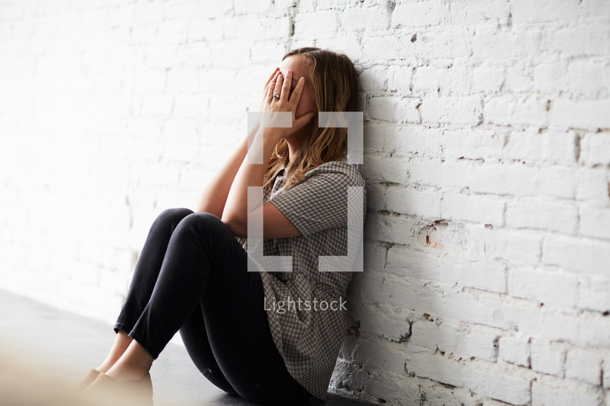 a woman crying covering her face with her hands