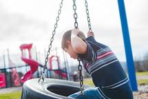 a boy child on a tire swing