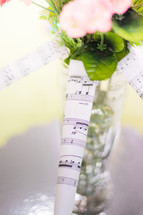 rolled up sheet music and a vase of flowers