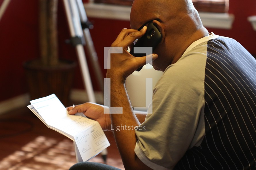 man talking on the phone, paying bills