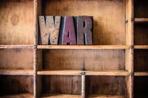 """Wooden letters spelling """"war"""" on a wooden bookshelf."""