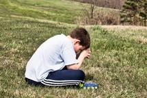 praying boy sitting in grass