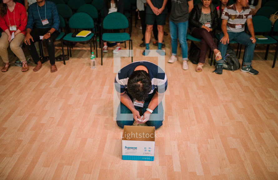 a man placing his sins in a box during a worship service