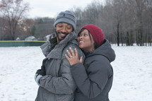 a couple hugging outdoors in snow