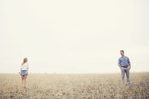 A man and woman stand far apart in a field of grass.