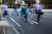 people walking across a crosswalk