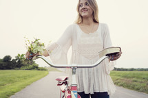 woman riding a bicycle holding a bible and flowers