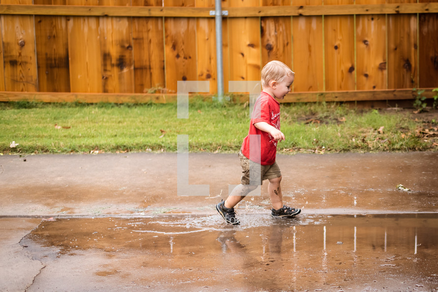 a toddler boy splashing in a puddle