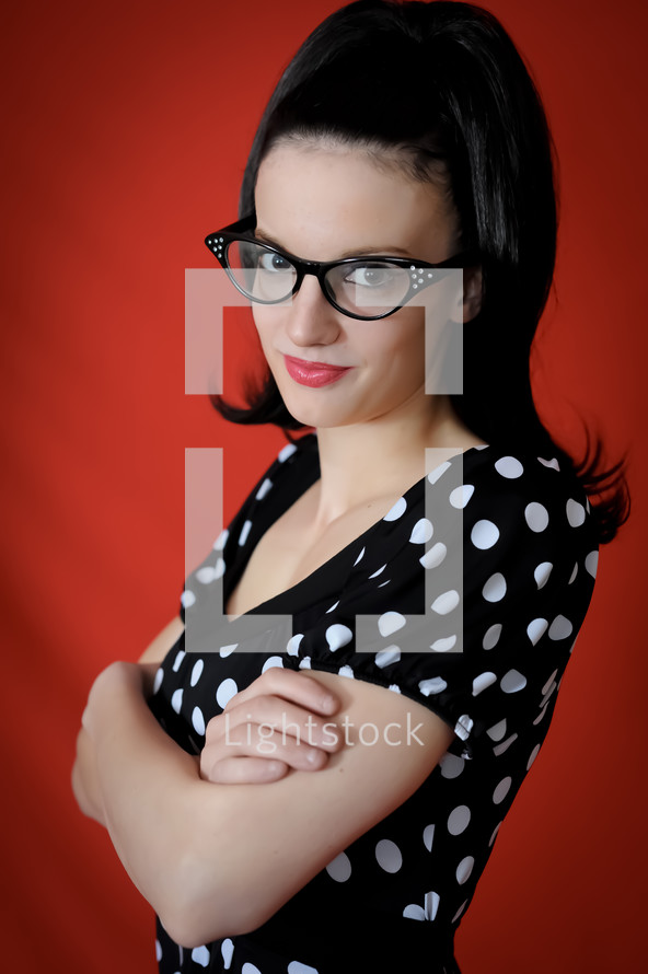Woman in cateye glasses with arms folded.