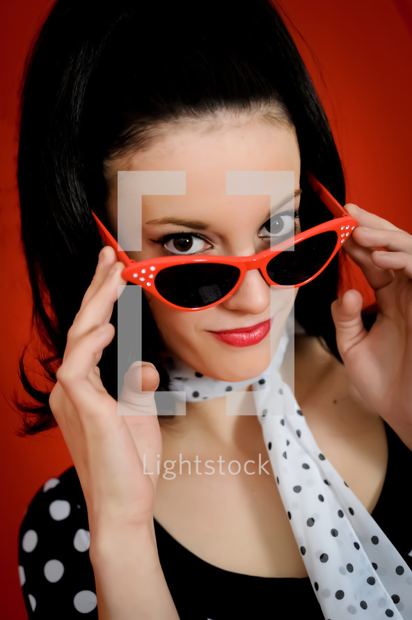 Woman looking over her cateye glasses.