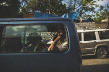 Passengers in a van traveling on a street through a village.