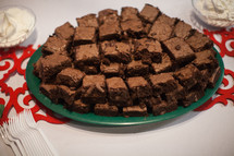 A plate piled with brownies on a table.